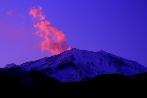 夕日を受けて燃え立つ水蒸気吹き上げる御岳山