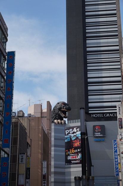 複合ビルの横にしがみつくゴジラ