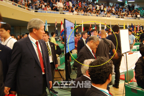 米国国籍の日系主審チームユース(黄色の円内)が韓国人の国際審判の激しい抗議に知らないふりを頭を下げている