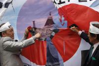 独立門の前で日本の総理大臣安部晋三の描かれた旗を切り裂く反日活動家