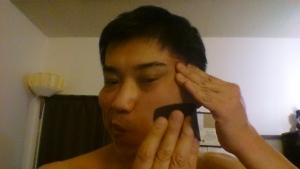 唇を尖らせてテープを貼る反対に寄せてこめかみを押さえながら大頬骨筋を引っ張りながら貼る