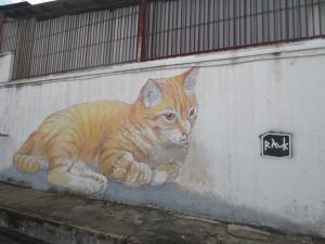 大きな猫の壁画。角を曲がるとネズミが隠れている壁画がある
