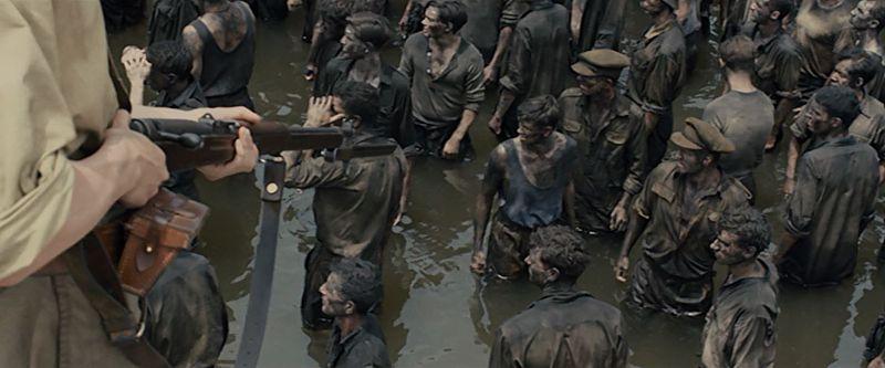 着剣した銃を向けられながら、川に入る汚れた捕虜たち
