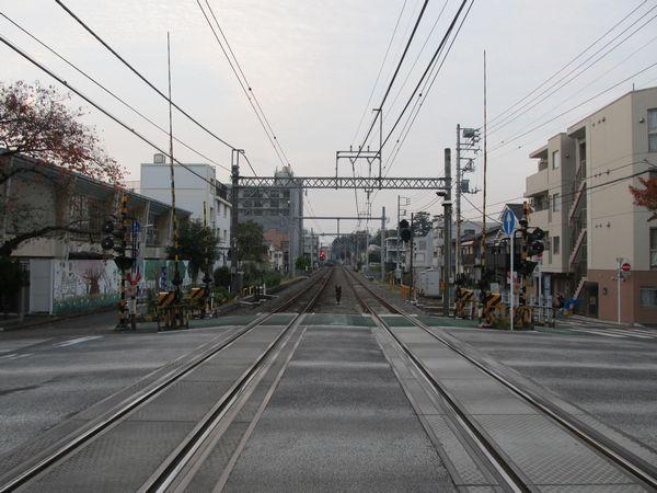 同じ踏切から本川越方面を見る。奥の赤く点灯している信号機が沼袋駅の場内信号機。